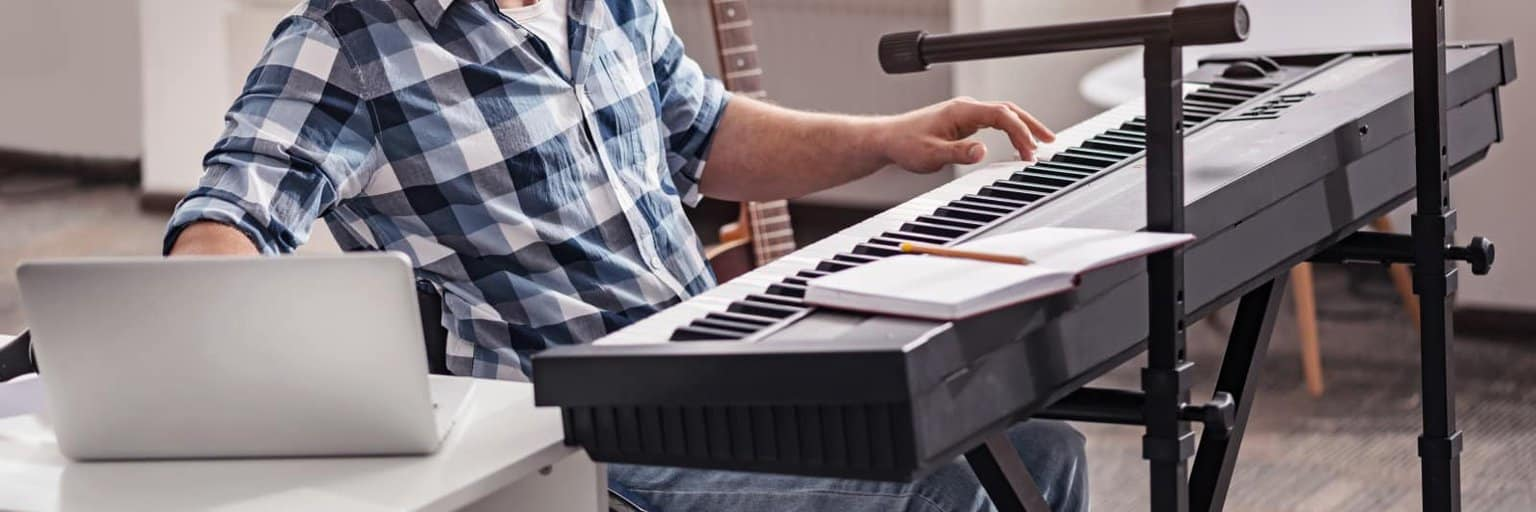 image of musician with keyboard and computer