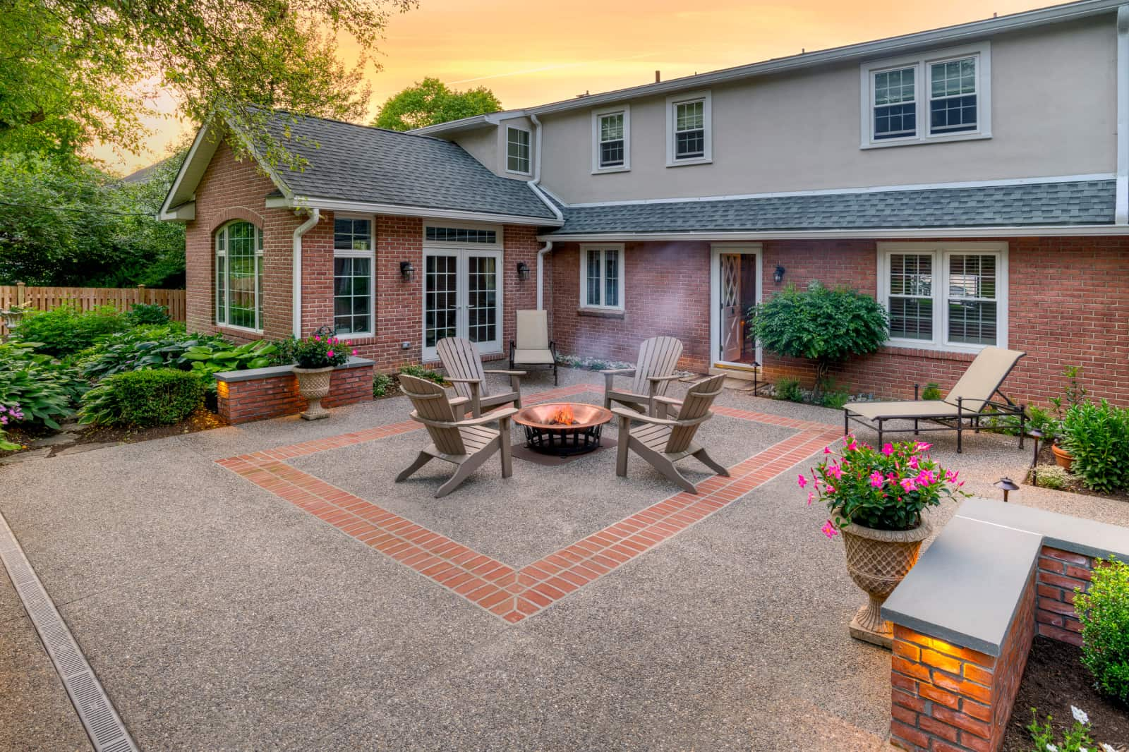 exposed aggregate-style backyard concrete patio with brick accent in the center and seatwall surrounding it
