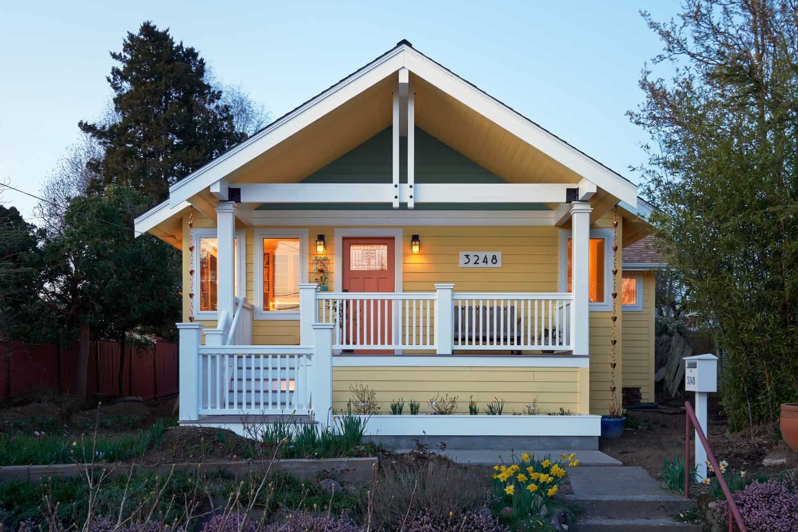 a soft yellow craftsman house with white trim, a bit of grey tone, and orange front door