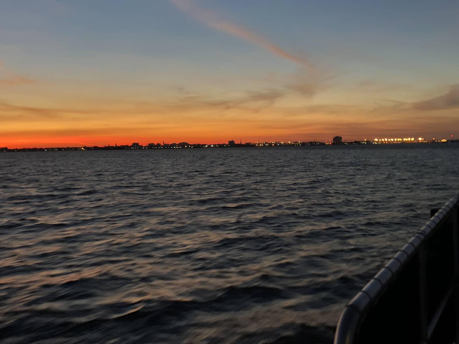 Blue to orange sunset over the city skyline. Sunset dolphin cruise Charleston, SC