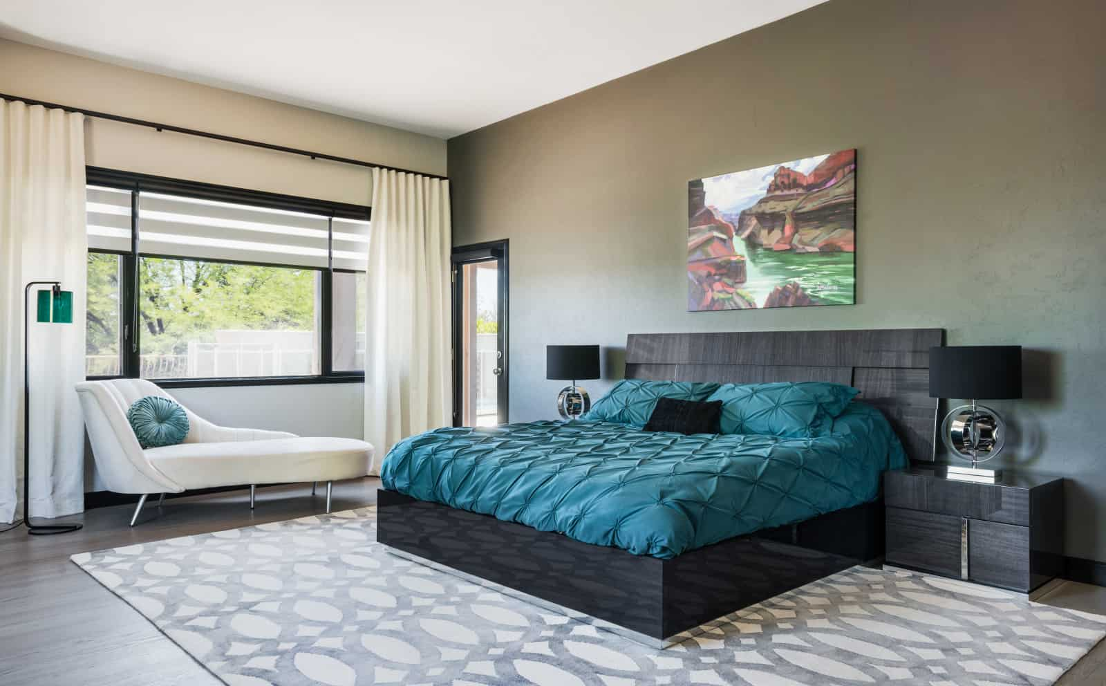 a black modern bed decorated with teal bedding set