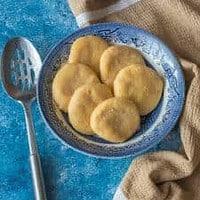 Jamaican cornmeal dumplings in a blue bowl