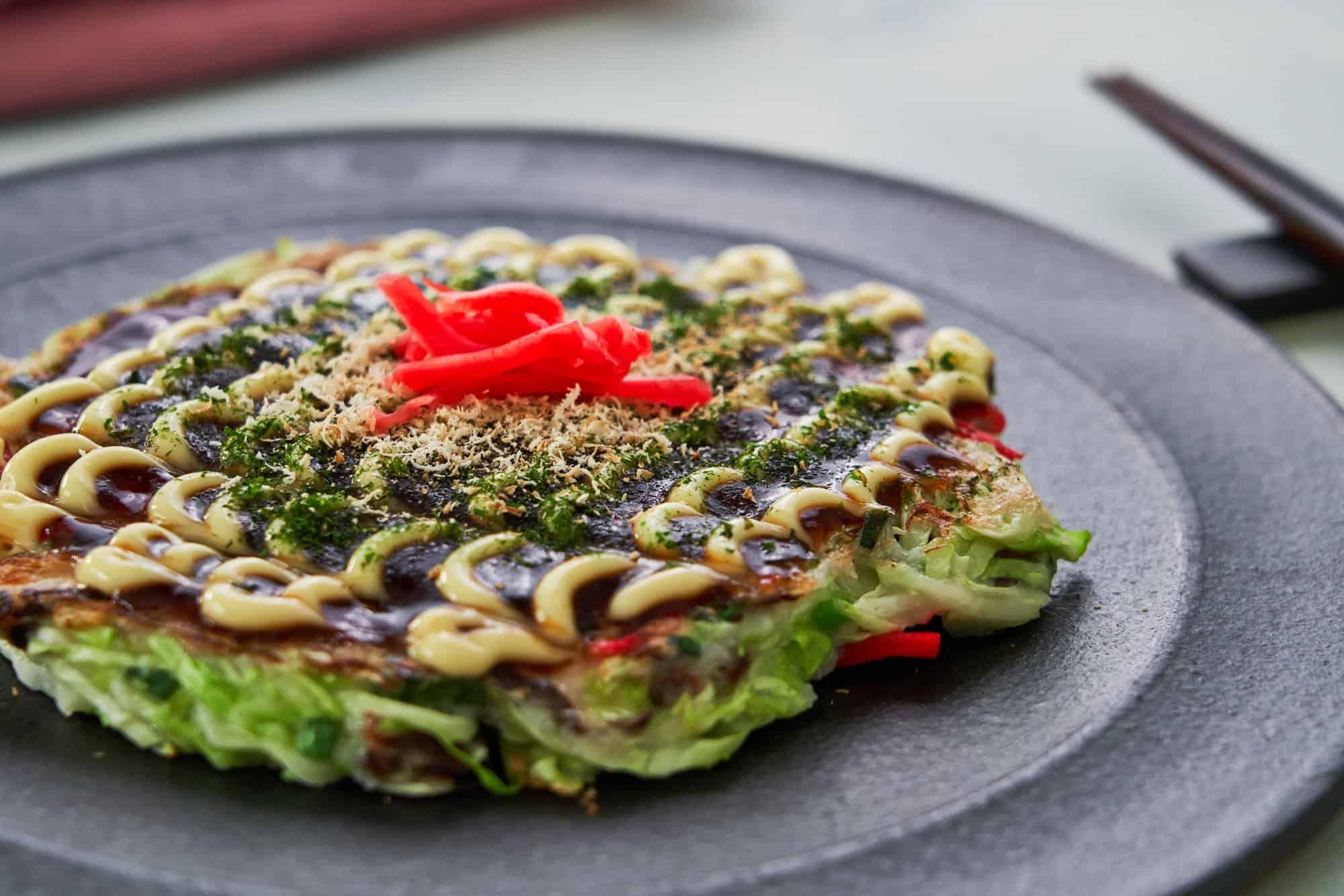 Vegan Okonomiyaki slathered in okonomiyaki sauce, plant-based mayonnaise, aonori, and dried shiitake mushroom flakes.