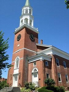 A brick church with a tall white steeple.