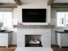 clean white tiles in front of cement mosaic fireplace, featuring beige walls and wood flooring