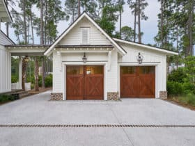use traditional barn doors to complete a large country-styled detached garage with breezeway