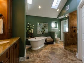 elevate a traditional bathroom with deep green walls and brown porcelain tile flooring
