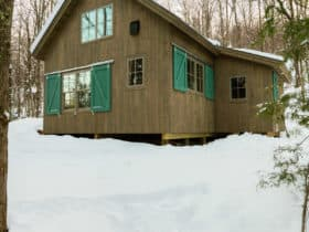 embellish a rustic mountain cabin with attractive forest green barn door window shutters