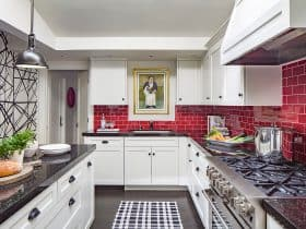 a red subway tile backsplash looks stunning in a black and white transitional kitchen interior