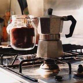Moka pot coffee brewing on a gas stove