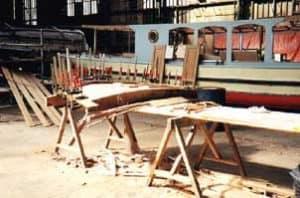 De houten rand van het dak van de slonboot Hilda met een paar houtklemmen.