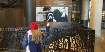 A girl checks out her pixelated image that moves with her at landmark near fenway park, boston