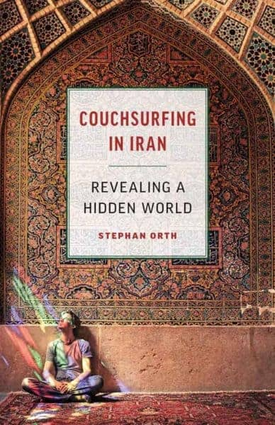 The author of couhsurfing in iran sitting in front of an elaborate persiab mural.