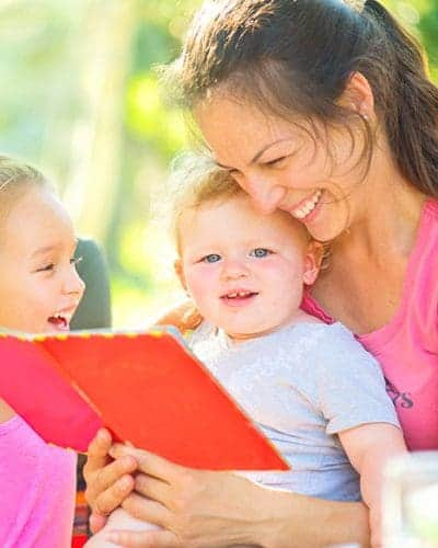 Tips-for-Homeschooling-while-paying-off-debt.-Mom-reads-library-books-to-her-kids
