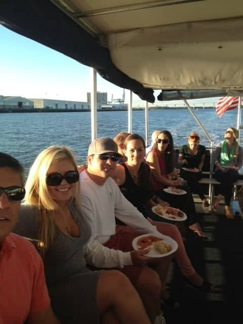 Part of a group party sitting and eating on the boat. Party boat rental Charleston, SC