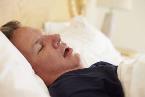 Man Asleep In Bed Snoring due to sleep apnea