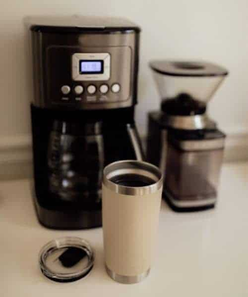 Cuisinart coffee maker on a counter next to a grinder