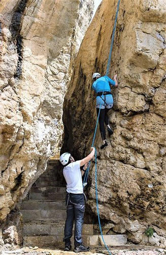 two climbers climbing rockface