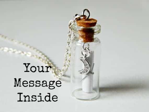 Small glass bottle with silver chain scroll and moon charm inside