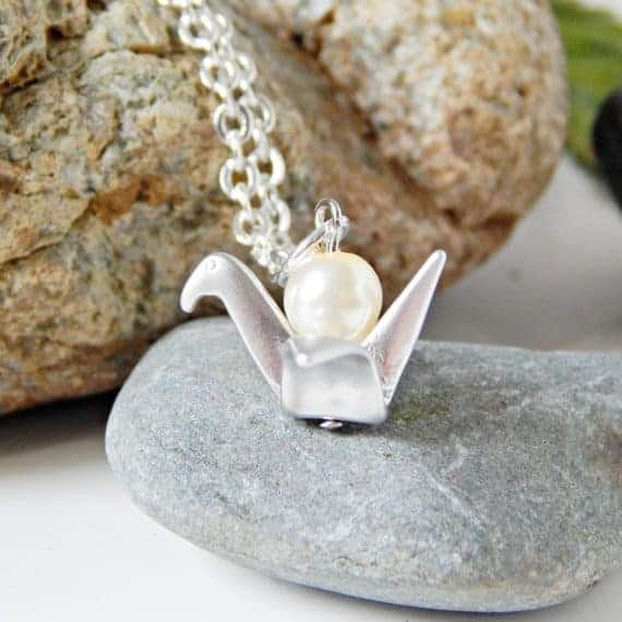 Silver crane necklace with ivory pearl displayed on river stone