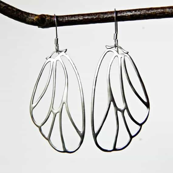 silver butterfly wing earrings hanging from branch