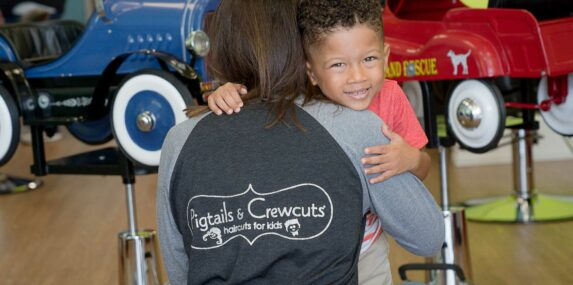 Kid hugging Pigtails & Crewcuts Stylist with Logo on Shirt