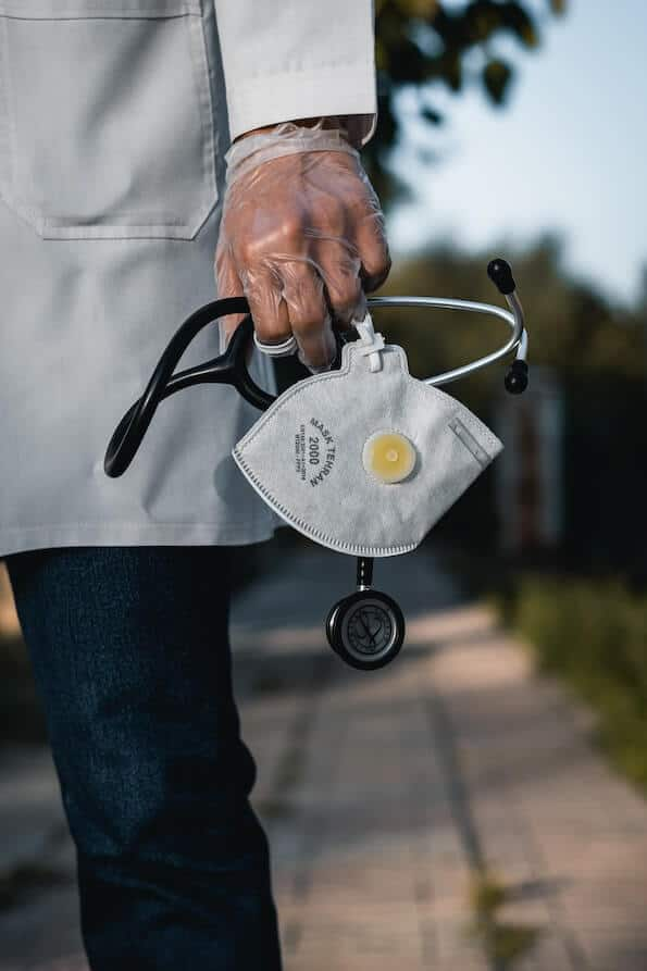 Doctor standing on walkway holding surgical mask and stethoscope in hand