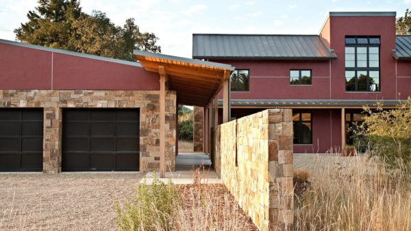 combine stone with concrete in this trendy stucco home featuring a detached garage and narrow breezeway