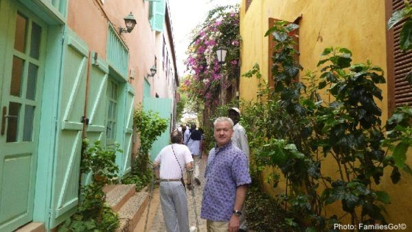 A goree alleyway with colorful flowers and brightly painted buildings
