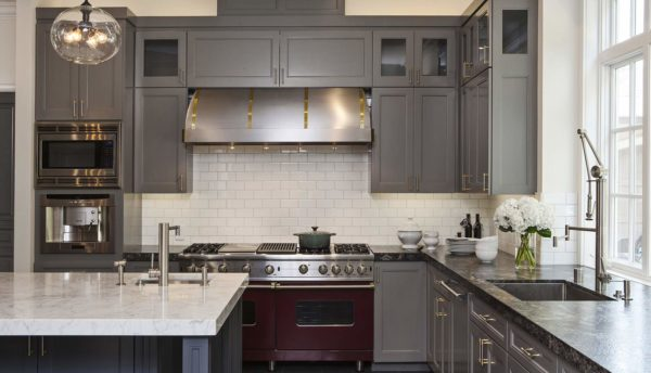 trendy kitchen featuring white tile backsplash stainless appliances and granite countertop