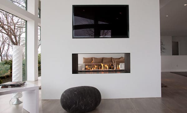 consider a black and white living room with a two-sided linear fireplace, mounted tv, and clean design