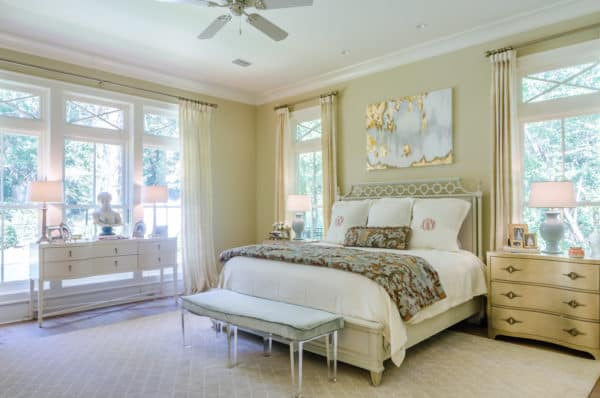 white bed with gold furniture and warm lighting creates a cottage-like oasis