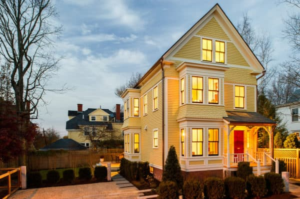 victorian style house with a charming red door and a grand three-story plan