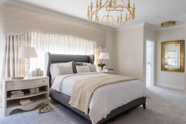 traditional yet cozy bedroom with white sheets and antique golden accessories