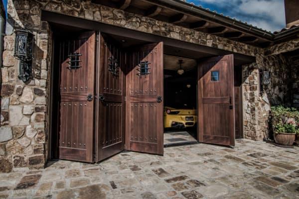folding barn style garage door features dark walnut color in a rural italian-style home