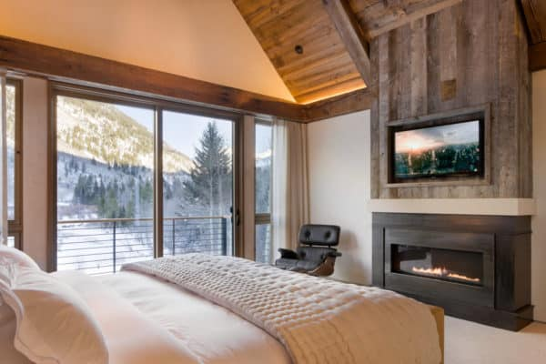 a rustic mountain-styled bedroom has a steel plate linear fireplace and reclaimed barnwood with tv above