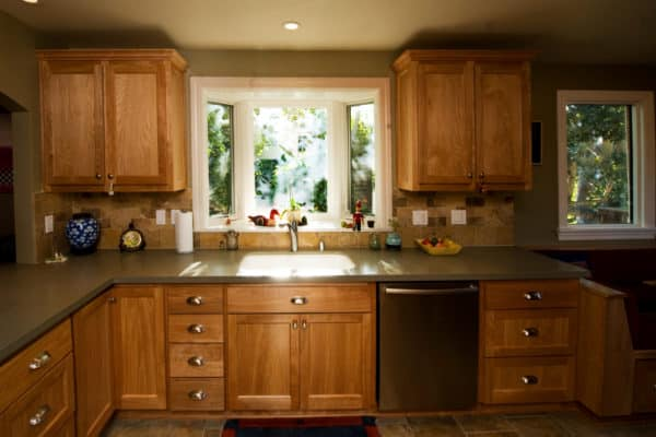 farmhouse kitchen looking cozy and warm with a bay window over sink and natural wood cabinets