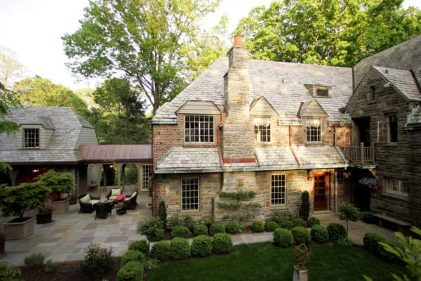 go back in time with a stunning stone build featuring a detached garage and breezeway with fairy lights