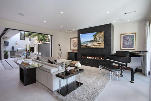 mix contemporary design and artistic touch for a rich seaside living room with linear fireplace and tv mount