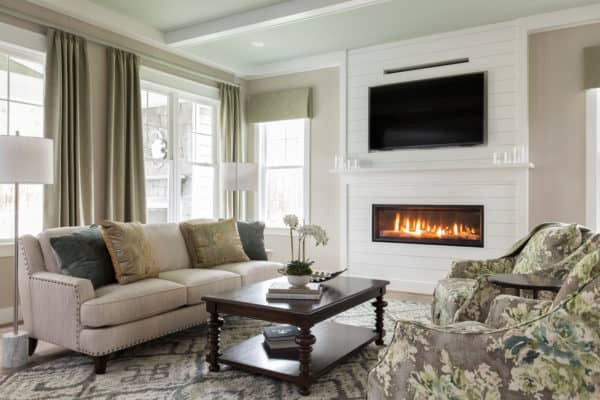 mix medium tone wood and white walls to enhance your linear fireplace with tv above in a comfy suburban home