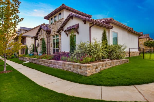 go for a mediterranean-inspired front yard retaining wall with concrete paver