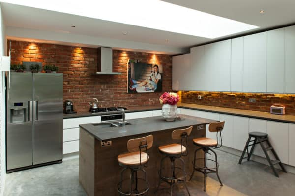 install real brick walls and place brown island for a chic and eclectic white kitchen