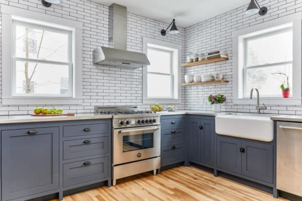 bring together custom blue cabinets and subway tile with black grout walls in a modern l-shaped kitchen