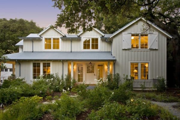 charming farmhouse home featuring white barn door window shutters in a beige exterior