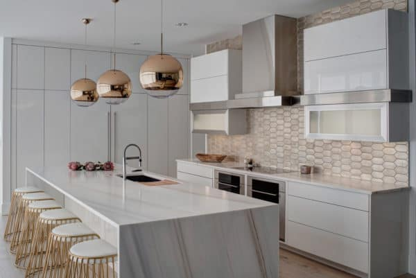 contemporary white kitchen with stainless appliances and brass gold details looks exquisite and stunning