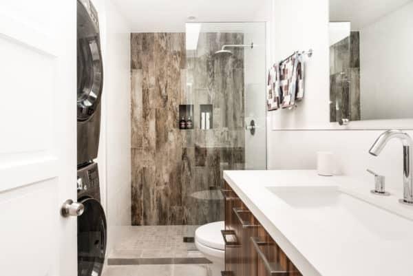 evoke luxury with quartz countertop and frameless shower door in this bathroom laundry combo
