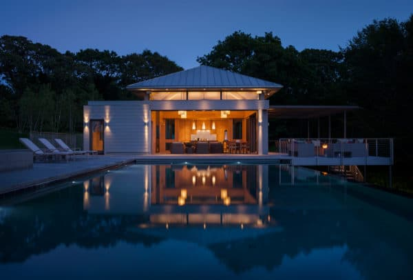 contemporary backyard and luxurious infinity pool featuring a modern pool house with bathroom