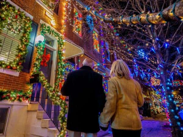 A couple admires the over-the-top lights on people's rowhouses on 13th street in south philly.