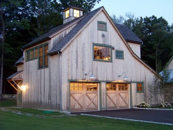 mountain-style cabin looks gorgeous with rustic cedar garage doors and pine siding