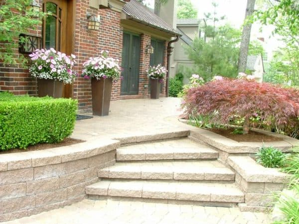 induce old-school charm in a red brick home with stone front yard retaining wall and huge vases